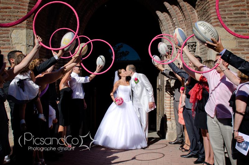 Sortie de l'église des mariés sous ballons de rugby et cerceaux de gym