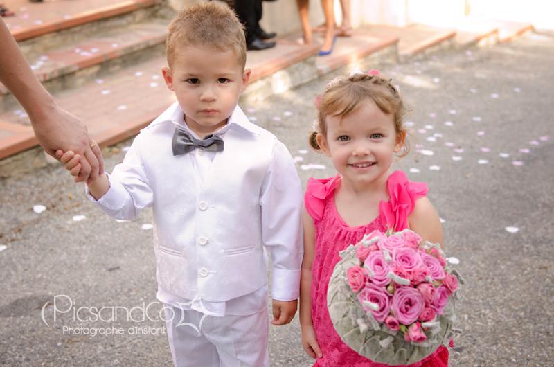 De beaux enfants fiers de toucher le bouquet de la mariée